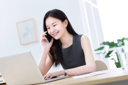 Jeune femme d'affaires au téléphone