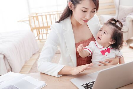 Young mother holding the children use the computer