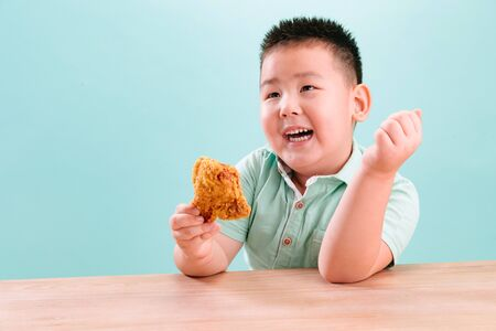 Lovely boy eating Fried chicken