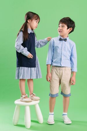Two children stood a stool