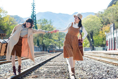 Young girlfriends walking together on the rail