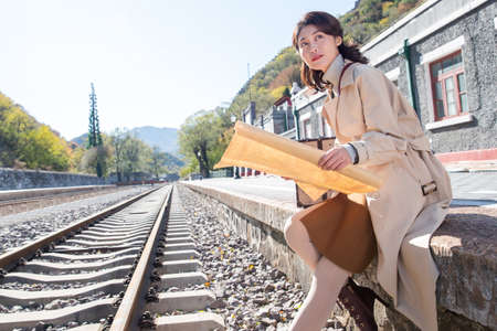 Young woman sitting next to track with map