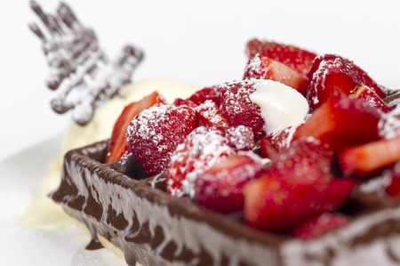 Belgian waffles with ice cream, dark chocolate and strawberries on white background
