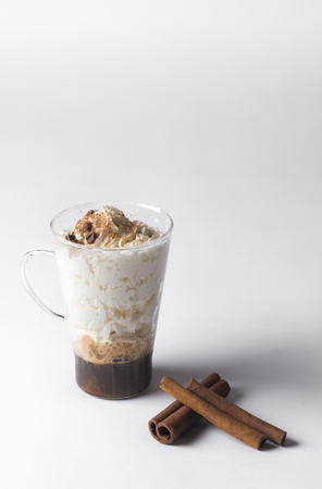 cold fresh ice coffee with cinnamon in white background