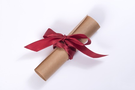 Scroll of old yellowed paper, bandaged a scarlet ribbon