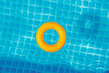 yellow Inflatable ring floating in swimming pool on sunny day, top view Banco de Imagens