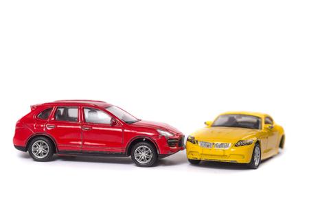 Accidente automovilístico entre coche rojo y coche amarillo aislado en blanco