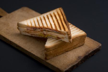 Club Sandwich auf einem Holzbrett auf dunklem Hintergrund