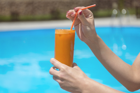 glass of fresh orange or carrot juice by the poolside