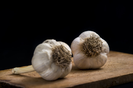 garlic on wooden board on black background
