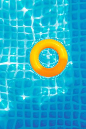 yellow Inflatable ring floating in swimming pool on sunny day, top view 版權商用圖片