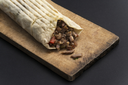 Doner kebab is on the cutting board. Shawarma with meat, onions, lettuce lies on a black background.