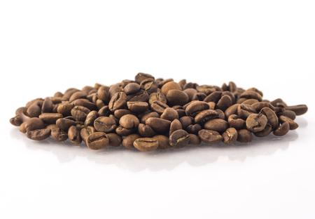 Geröstete Kaffeebohnen stapeln sich auf Weiß Standard-Bild