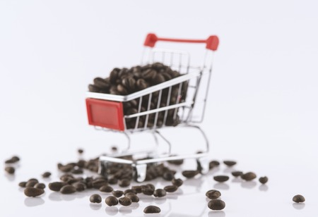 A lot of coffee beans are in the shopping cart. Фото со стока