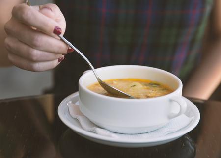 Frauenhand mit dem Löffel beim Essen der Suppe im Restaurant Standard-Bild