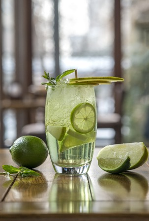 fresh lemonade with citrus and apple on wooden table