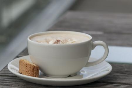 Café capuchino en una taza blanca sobre una mesa de madera