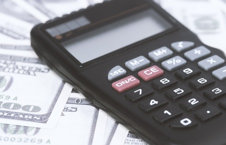 A few dollars and a calculator on the table, finance and savings.Business concept