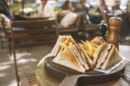 Club sandwich on wooden board on a table in a cafe 免版税图像