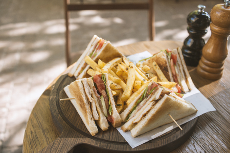 Club sandwich on wooden board on a table in a cafe Stock Photo