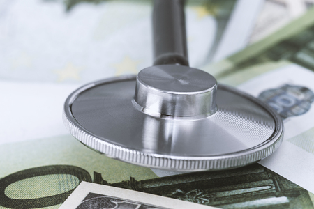 Medical stethoscope on dollars and euro banknotes