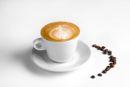 Café latte dans une tasse à café blanche avec plaque sur blanc Banque d'images