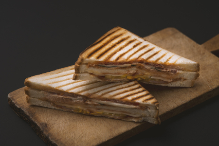 Club sandwich on a wooden board on a dark Stock Photo