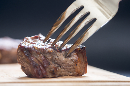 Piece of meat on a fork, dark