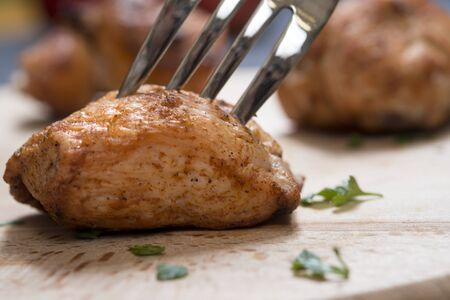 Piece of chicken meat on a fork, food concept