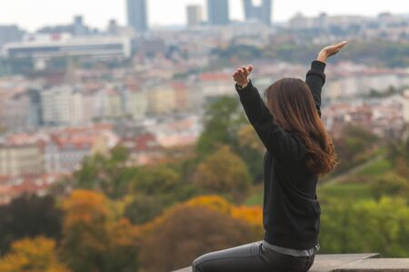 Woman raises up arms in the air and looks at the city from above
