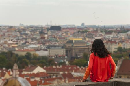 View from back. Woman enjoying the view of the city on an autumn day 免版税图像