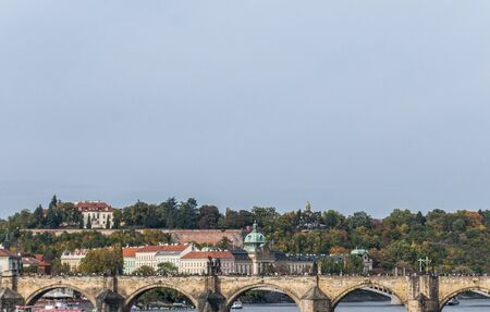 View to the historical bridges, Prague old town and Vltava river from popular view point in the Letna park (Letenske sady), beautiful autumn landscape in soft yellow morning light, Czech Republicn