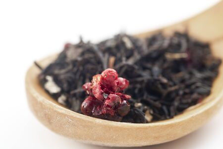 aromatic black dry tea with raspberries on a wooden spoon isolated on white background