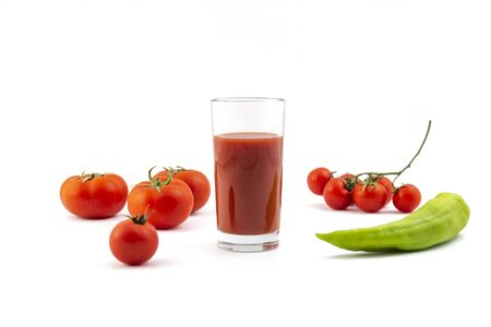 Glass with fresh tomato juice , pepper and tomatoes on a white background Фото со стока