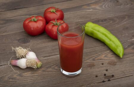 Glass with fresh tomato juice , pepper and tomatoes on a wooden background