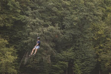 Tourist ride on the Zipline through the canyon. Tourist in helmets is riding on a cable car