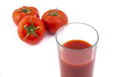 Tomato juice in a glass and ripe tomatoes on a white background