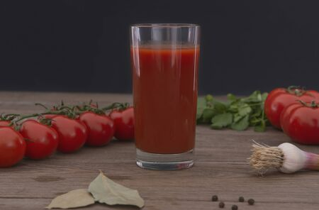 Glass with fresh tomato juice , garlic and tomatoes on a wooden background