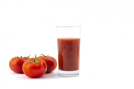 Glass with fresh tomato juice  and  tomatoes on a white background