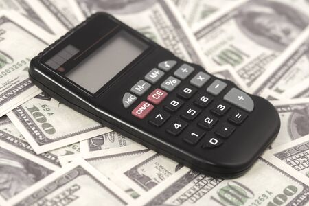 A few dollars and a calculator on the table, finance and savings.Business concept Stockfoto
