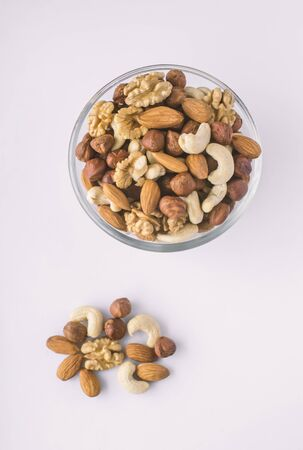 Mixed nuts in a bowl on a white background.Top view and copy space