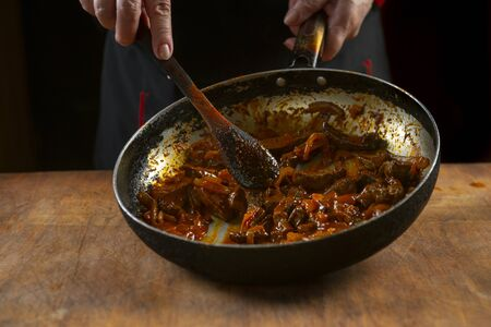 Chef cooks Chinese food in a pan, stirring with a wooden spoon