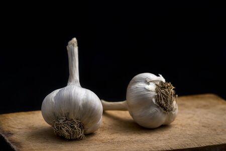 Garlic on wooden board on black