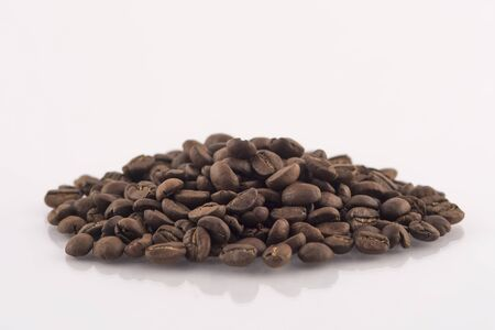 Roasted coffee beans pile on white