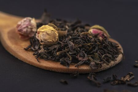 Aromatic black dry tea with rose flowers on a wooden spoon isolated on black 版權商用圖片