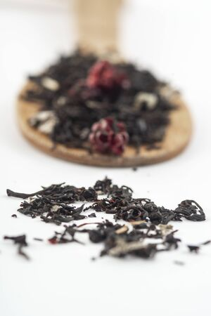 Aromatic black dry tea with raspberries on a wooden spoon isolated on white