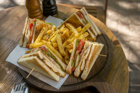 Club sandwich on wooden board on a table in a cafe 写真素材