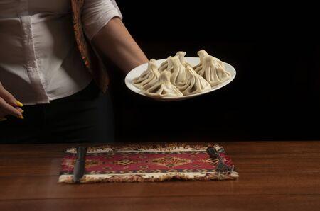 Waiter brings a plate of khinkali.Georgian cuisine. 版權商用圖片