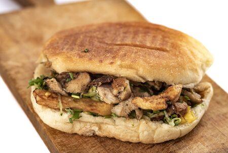 Shawarma sándwich oriental, doner kebab, giroscopios en una mesa de madera sobre fondo blanco.