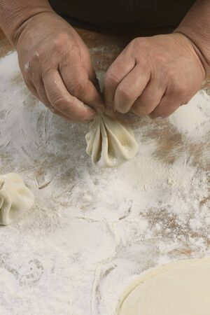 Chef cook making khinkali  on wooden table. Process preparation georgian meal. food concept.